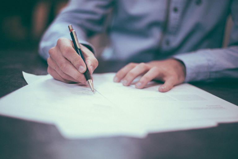 Mann in blauem Hemd unterschreibt einen Vertrag