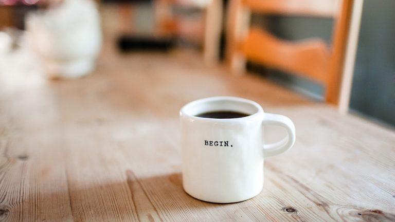 weißer kaffebecher mit aufschrift begin. auf einem holztisch