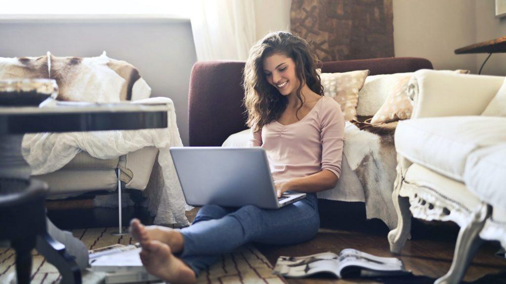 frau benutzt lächeln laptop vor sofa