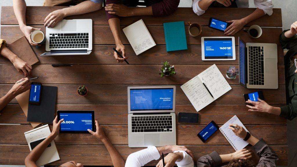 menschen sitzen um einen tisch mit geöffneten laptops
