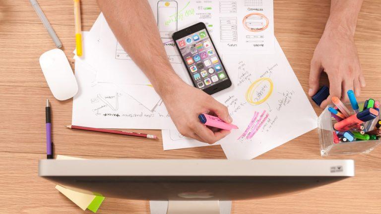 schwarzes iphone im homescreen auf beschriebenem papier auf tisch mit stift und monitor