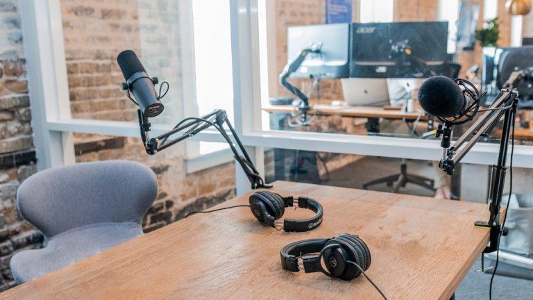 kopfhörer und mikrophon auf einem braunen tisch in einem büro