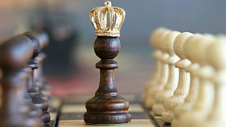 schwarze Schachfigur mit Krone auf schachbrett