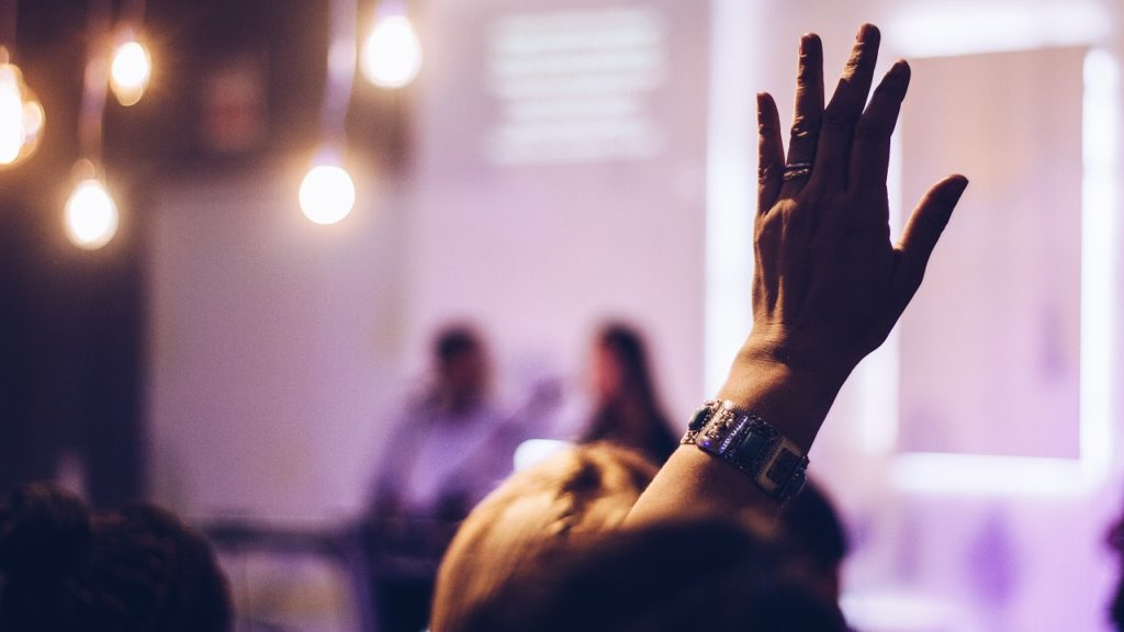 person hebt hand bei vortrag