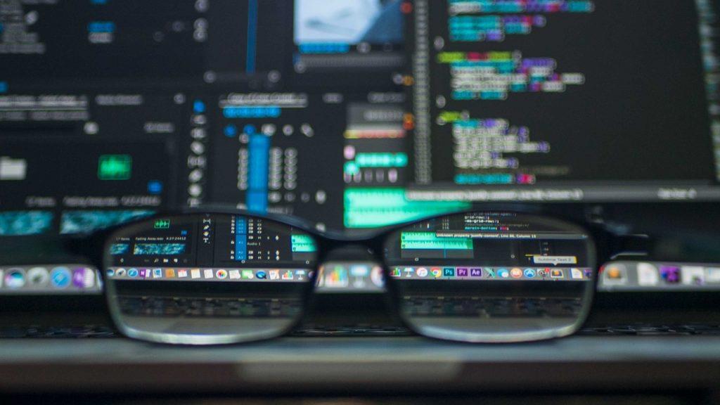 brille vor zwei monitoren mit code