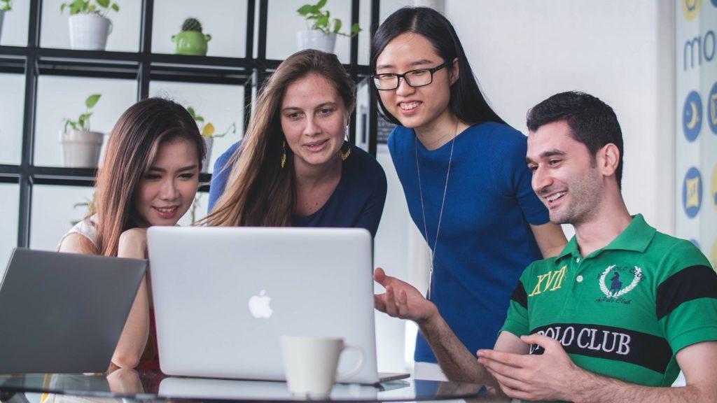 vier menschen schauen auf einen silbernen laptop
