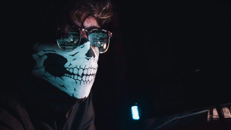 mann mit totenkopfmaske und brille vor monitor