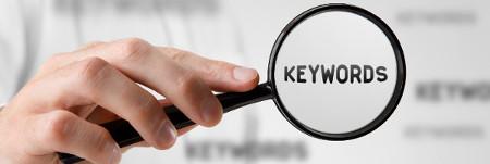 Eine Hand hält eine Lupe, in der sich der Begriff Keywords befindet.