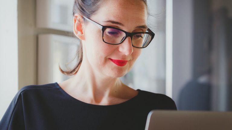 frau mit brille sitzt vor silbernen laptop