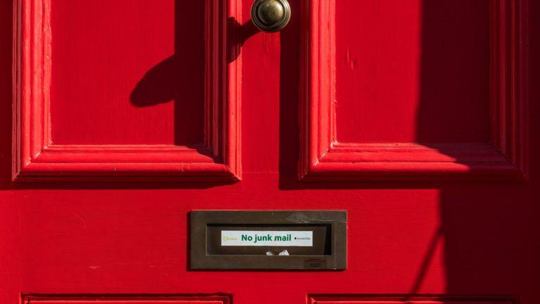 rote tür mir briefkasten mit aufschrift no junk mail